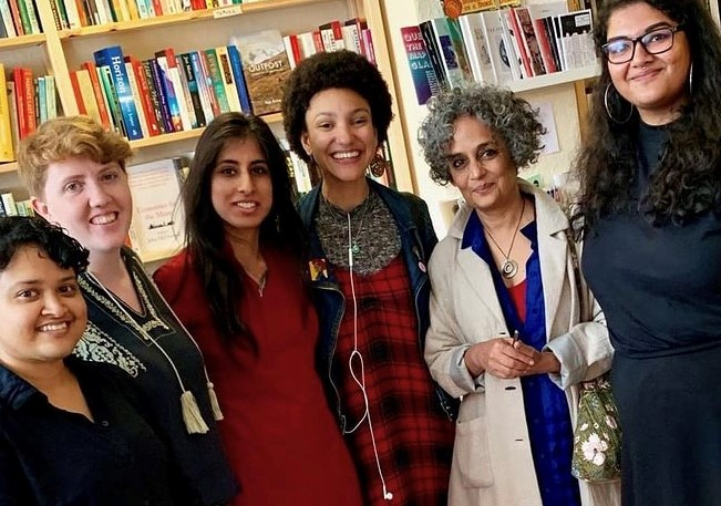 Arundhati Roy standing in lighthouse surrounded by Lighthouse keepers